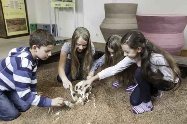 Kinder legen ein Skelett frei